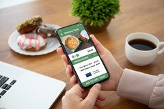 Female hands holding phone with app delivery food on screen. Female hands holding phone with app delivery food on the screen above the table in the office stock photo