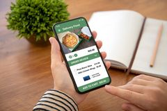 Female hands holding phone with app delivery food on screen. Above the table in office royalty free stock images