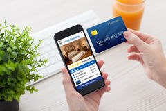 Female hands holding phone app hotel booking and credit card. Female hands holding phone with app hotel booking screen and credit card in office stock image