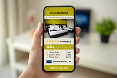 Female hands holding phone with app hotel booking on screen. Female hands holding phone with app hotel booking on the screen in the house in room stock photo