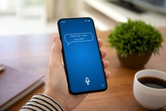 Female hands holding phone with app personal assistant on screen. Female hands holding touch phone with app personal assistant on screen above the table in the royalty free stock image