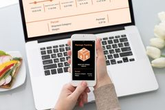 Female hands holding phone with app tracking delivery package sc. Female hands holding phone with app tracking delivery package on screen laptop background Royalty Free Stock Images