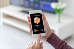 Female hands holding phone with app tracking delivery package sc. Female hands holding phone with app  tracking delivery package screen in room home Royalty Free Stock Photo