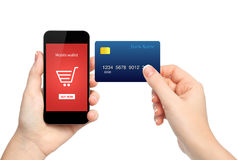 Female hands holding phone and credit card making a online purch Royalty Free Stock Photography