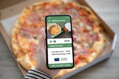Female hands holding phone with delivery food app pizza box. Female hands holding phone with delivery food app on the screen above pizza box royalty free stock photo