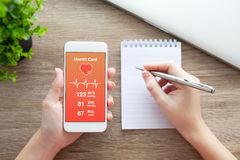 Female hands holding phone with health card on the screen Stock Image