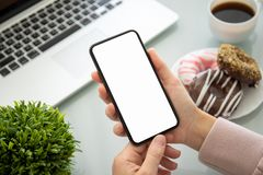 Female hands holding phone with isolated screen above the table. In office royalty free stock photos