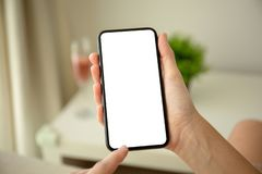 Female hands holding phone with isolated screen in the room. Female hands holding phone with isolated screen in the house in room stock image