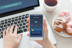 Female hands holding phone with online air ticket and laptop Royalty Free Stock Photography