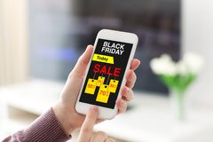 Female hands holding phone with sale black Friday screen. In room home Stock Photography