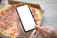 Female hands holding phone with  screen above pizza box. Female hands holding phone with  screen above the pizza box royalty free stock photography