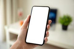 Female hands holding phone with  screen in the room. Female hands holding phone with  screen in the house in room stock images