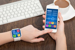 Female hands holding phone smart watch with app smart home. Female hands holding touch phone and smart watch with app smart home on screen royalty free stock photo