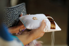 Female hands holding pillow with wedding ring. Female hands holding pillow with golden wedding ring Stock Images