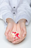 Female hands holding pills and capsules Stock Image