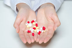 Female hands holding pills and capsules. Royalty Free Stock Images