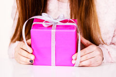 Female hands holding pink gift box with ribbon. Closeup of female hands holding pink gift box with silver ribbon, girl with christmas present. Birthday, holidays Royalty Free Stock Photo