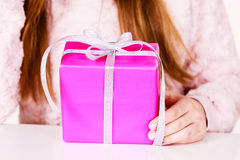 Female hands holding pink gift box with ribbon. Closeup of female hands holding pink gift box with silver ribbon, girl with christmas present. Birthday, holidays Stock Image