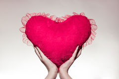 Female hands holding a pink or red plush heart Royalty Free Stock Images