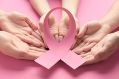 Female hands holding pink ribbon on color background. Breast cancer awareness concept stock images