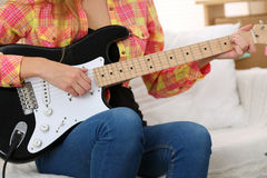 Female hands holding and playing black electric guitar closeup Royalty Free Stock Images