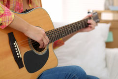 Female hands holding and playing western acoustic guitar closeup Royalty Free Stock Image