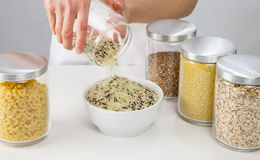 Female hands holding a pot with raw rice Royalty Free Stock Photography