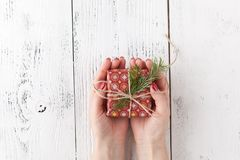 Female hands holding present with twine bow on white rustic background. Festive backdrop for holidays: Christmas, New Year. Flat l Stock Images