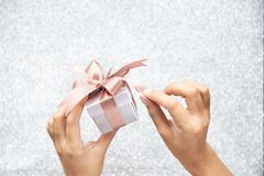 Female hands holding or pulling ribbons of a small gift box with copy space for text. royalty free stock images