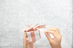 Female hands holding or pulling ribbons of a small gift box stock images
