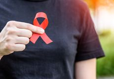 Female hands holding red AIDS awareness ribbon. Aids Awareness campaign royalty free stock image