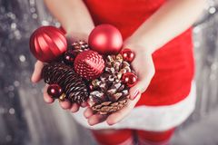 Female hands holding red Christmas decorations and cones, shiny xmas background. Holiday gift and ornaments. Toning stock image