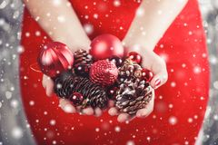 Female hands holding red Christmas decorations and cones, shiny xmas background. Holiday gift and ornaments. Toning royalty free stock photos