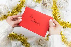 Female hands holding a red envelope with text `To Santa` stock photos