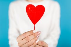 Female hands holding a red heart. On blue background royalty free stock photography