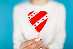 Female hands holding a red heart. On blue background royalty free stock photos