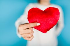 Female hands holding a red heart. On blue background royalty free stock photo