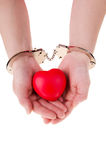 Female hands holding red heart. Female in handcuffs holding red heart, isolated on white background stock photo