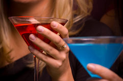 Female Hands Holding a Red Martini. Hands holding a red and a blue martini stock photo