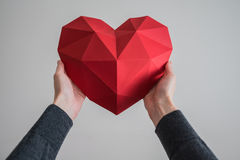Female hands holding red polygonal heart shape. Two female hands holding red polygonal paper heart shape royalty free stock photography