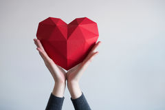 Female hands holding red polygonal heart shape. Two female hands holding red polygonal paper heart shape royalty free stock images