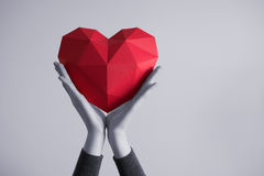 Female hands holding red polygonal heart shape. Two female hands holding red polygonal paper heart shape. Tonned image stock photography