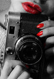 Female hands holding retro camera. Black-and-white photo, red lips, red nails. Vertical photo Stock Image