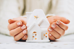 Female hands holding and saving small house Royalty Free Stock Image