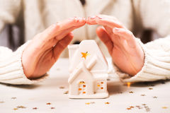 Female hands holding and saving small house Royalty Free Stock Photo