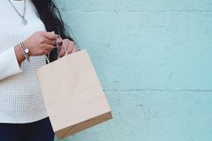 Female hands holding shopping bag outdoors. royalty free stock image