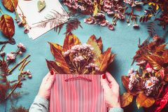 Free Female Hands Holding Shopping Bag With Autumn Flowers And Leaves Bunch On Blue Table Background Stock Image - 124682581
