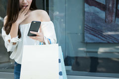 Female hands holding a shopping bags and look a smartphone shock. stock photos