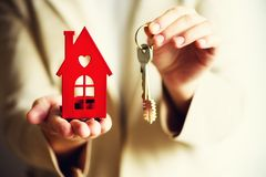 Female hands holding small red house and keys. Real estate agent offer you house or apartment. Property insurance and. Security concept. Copy space Royalty Free Stock Image