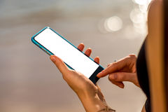 Female hands holding smartphone on the beach stock photo